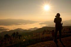 Fotógrafo que toma el cuadro del paisaje Imagen de archivo libre de regalías