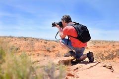 Fotógrafo que toma a foto com câmara digital profissional Imagem de Stock