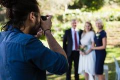 Fotógrafo que toma a foto da noiva e dos seus pais fotos de stock royalty free