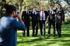 Fotógrafo que toma a foto do noivo e dos groomsmen imagem de stock royalty free