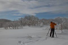 Fotógrafo que toma imágenes de un paisaje agradable de una montaña congelada Imagen de archivo