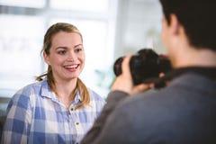 Fotógrafo que toma a imagem do colega feliz no escritório criativo imagem de stock