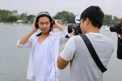 Fotógrafo que toma la imagen del modelo en fondo del río de la naturaleza Imagen de archivo libre de regalías