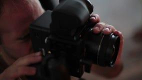 fotógrafo que toma las fotografías con la cámara digital del slr metrajes