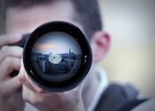 Fotógrafo que toma un cuadro en puesta del sol Foto de archivo
