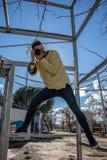 Fotógrafo que toma una imagen que lleva una camisa amarilla en una posición de la acción imágenes de archivo libres de regalías