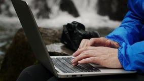 Fotógrafo que trabaja en un ordenador en un fondo de la cascada metrajes