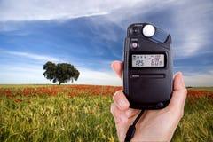 Fotógrafo que usa el fotómetro para medir la luz foto de archivo libre de regalías