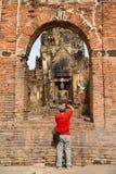 Fotógrafo rojo de la camisa que tira la imagen hermosa de Buda de la roca Imagenes de archivo