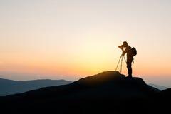 Fotógrafo sobre a montanha no fundo do por do sol Imagens de Stock