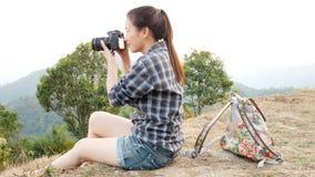 Fotógrafo turístico asiático activo joven del viaje de la mujer con una mochila que toma imágenes por la cámara digital en el pun metrajes