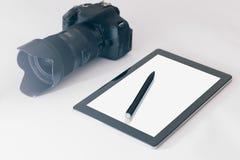 Fotógrafo Workspace na tabela, na tabuleta e na câmera brancas s branco fotografia de stock