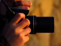 Fotógrafo y su cámara en la puesta del sol Fotografía de archivo libre de regalías