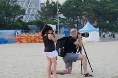 Fotógrafos en la playa, el hombre y la hija Fotografía de archivo libre de regalías