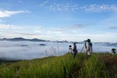 2 fotógrafos y el pequeño pueblo en la niebla, algo donde cerca de Dalat, Vietnam Foto de archivo