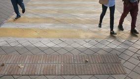 Fotövergångsställe Folket korsar vägen Fot som går på trottoaren lager videofilmer