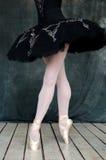 Fot av en ballerina i svart klänning på trägolv Arkivbild