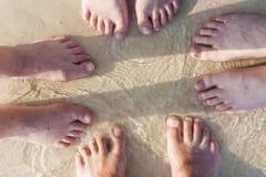 Fot av en familj i den fina sanden Arkivfoton