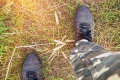 Fot av en man i smutsiga skor och kamouflerade flåsanden Royaltyfria Bilder