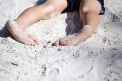 Fot av en pojke som spelar i sanden Arkivbild