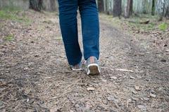Fot av en rinnande kvinna i skogen Arkivbilder
