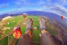 Fot av flickan i sportskor över kanten i den blåa himlen fotografering för bildbyråer