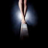 Fot av gymnasten på balansbommen Arkivbild