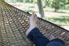 fot av kvinnan som vilar och att koppla av och att sova på rottingvagga i gummin Royaltyfria Bilder