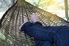 fot av kvinnan som vilar och att koppla av och att sova på rottingvagga i gummin Fotografering för Bildbyråer
