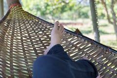 fot av kvinnan som vilar och att koppla av och att sova på rottingvagga i gummin Royaltyfri Fotografi