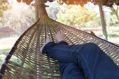 fot av kvinnan som vilar och att koppla av och att sova på rottingvagga i gummin Royaltyfri Bild