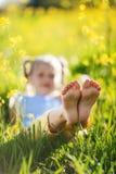 Fot av lilla flickan i gult fält med blommor arkivbild