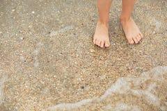 Fot barn på en sandig strand med snäckskal Arkivbild
