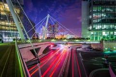 Fot- bro och moderna byggnader som är närgränsande till en väg på nig Royaltyfri Bild