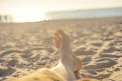 Fot closeup på stranden på den sunbed tyckande om solen på solig sommardag Royaltyfria Bilder