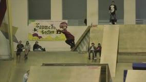 Fot för rullskateboradåkarehastigt grepp i hopp språngbräda Extremt jippo Konkurrens i skatepark folk arkivfilmer