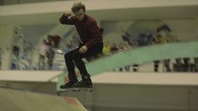Fot för rullskateboradåkarehastigt grepp i hoppet, flip 180 språngbräda Extremt jippo Konkurrens i skatepark stock video