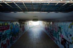 Fot- gångtunneltunnel med målat av grafitti på väggen Arkivfoton