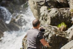 Fot?grafo profissional da paisagem que dispara em uma cachoeira fotos de stock royalty free