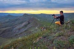 Fot?grafo profissional que usa um trip?, tomando uma foto de uma paisagem da montanha imagens de stock