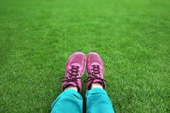 Fot i gymnastikskor i grönt gräs arkivfoto