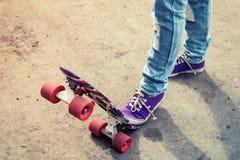 Fot i jeans och deckare på en skateboard Arkivfoton