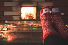 Fot i röda sockor vid spisen Kopplar av, genom varmt brand och att värma hennes fot i julsockor upp Santa Claus och rött klumpa i Royaltyfria Bilder