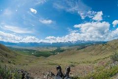 Fot i skorna mot bakgrunden av bergen Royaltyfri Foto