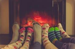 Fot i sockor allra familjen som värme vid hemtrevlig brand Arkivfoto