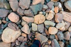 Fot i trendiga sandaler på lösa stora stenar Arkivbild