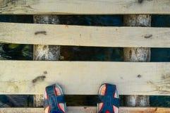 Fot i trendiga sandaler på träbron med att flöda för vatten Royaltyfri Fotografi