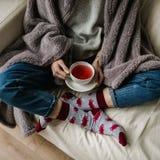 Fot i ull- sockor Kvinnan är avslappnande med en kopp av varm drink och uppvärm av hennes fot i ull- sockor upp royaltyfri foto