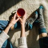 Fot i ull- sockor Kvinnan kopplar av med en kopp av varm drink och uppvärm av hennes fot i ull- sockor upp Slut upp på fot Övervi Royaltyfri Foto