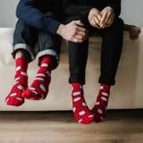 Fot i ull- sockor Para att koppla av med en kopp av den varma drinken och uppvärm av deras fot i ull- sockor upp Arkivbild